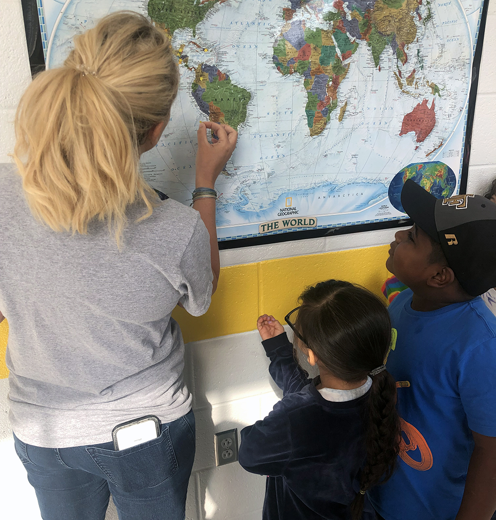 Academy second-grade teacher, Kori Trainor '10, and students, Kaylee Trejo and Brandon Marcial Santos, push pins into a map showing the countries represented by students. Photo submitted