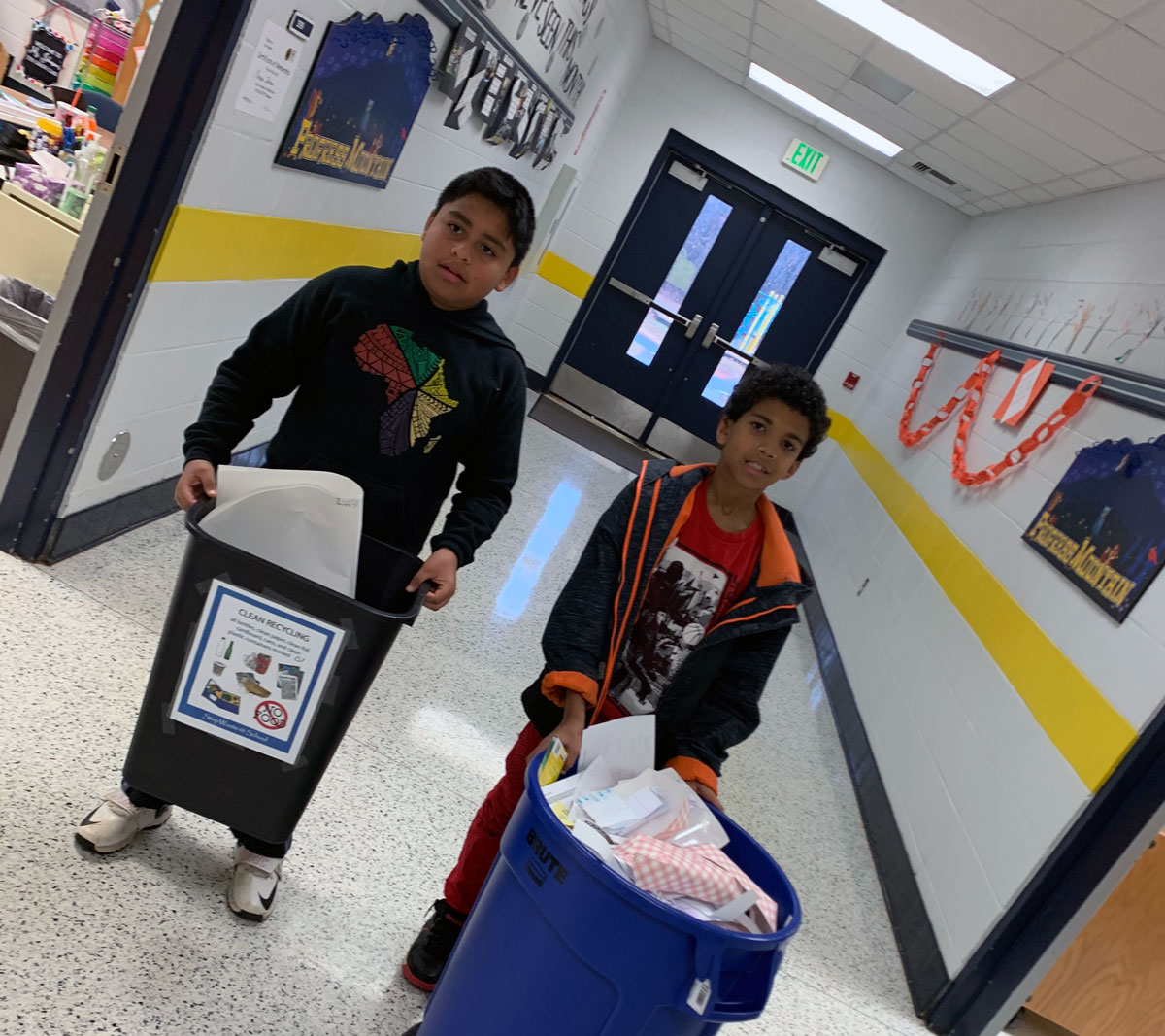 Students Angel Zamora-Perez and Josiah Jones help collect recycling from the classrooms.