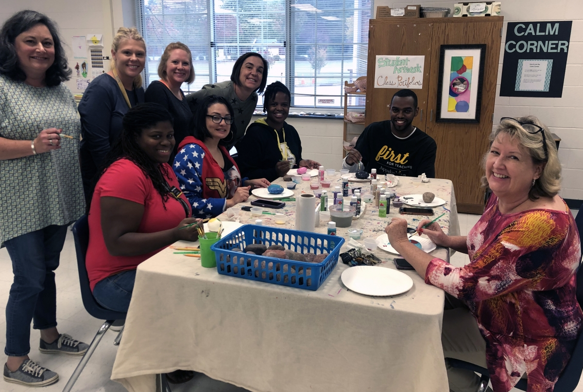 Academy teachers and staff paint their identity rocks. Photo submitted