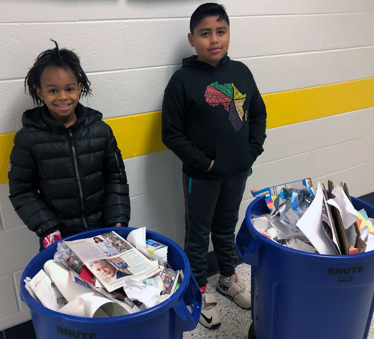 Students Rajanae Bethea and Angel Zamora-Perez show off how much recycling they have collected.