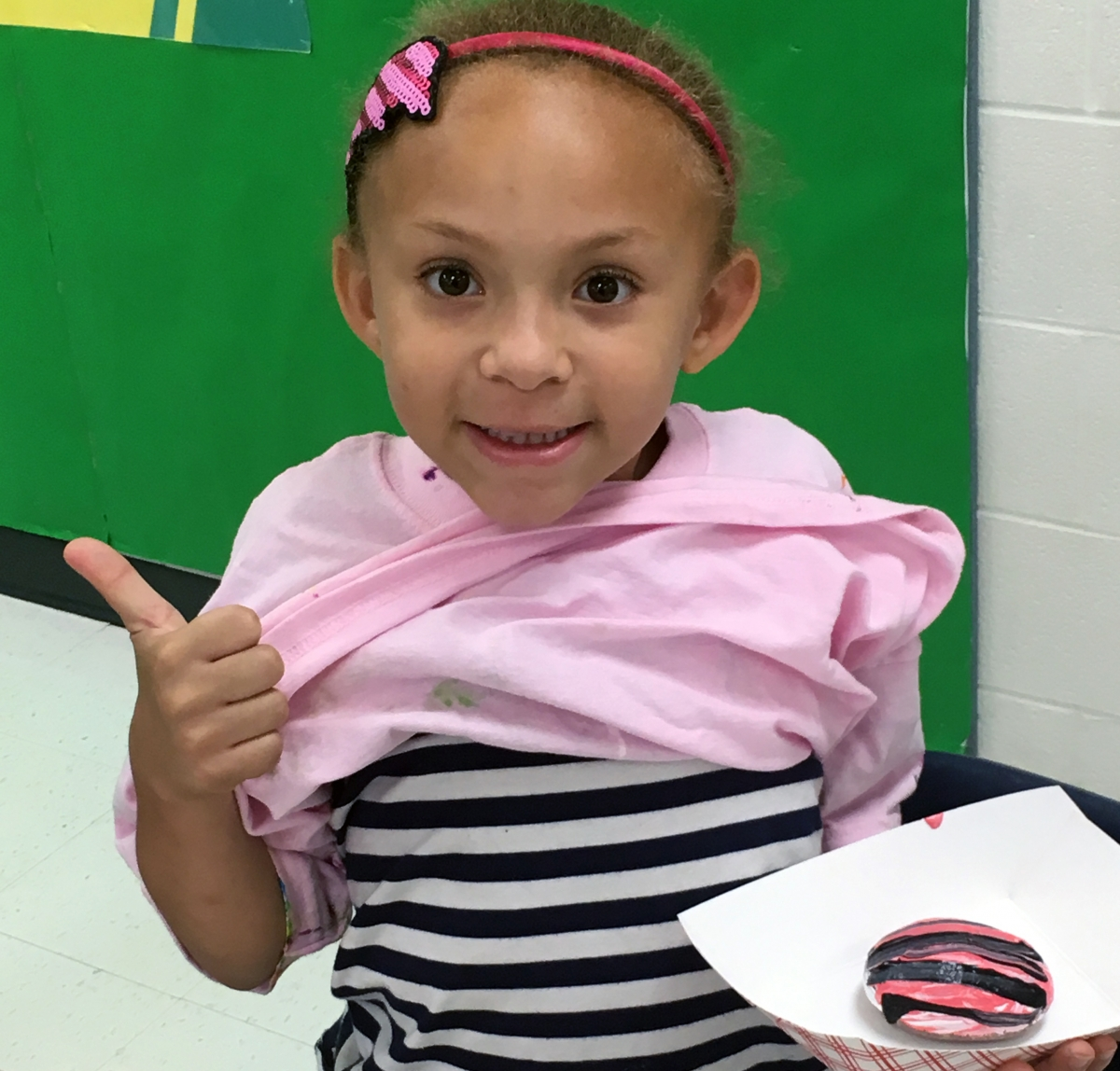 Academy first grader, Kaylee Simmons, shows off her rock painted with the same colors and pattern of the shirt she was wearing that day. Photo submitted