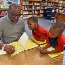 """Derrick Barnes signs a copy of his book """"Crown: An Ode to the Fresh Cut"""" for Middle Fork Academy kindergarten students Bradley Stafford (center) and Marlon Nelums on Wednesday. Barnes is a winner of the John Newbery Medal and the Caldecott Medal, among other honors."""