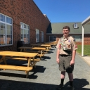 Boy Scout Ryan Porter with the eight picnic tables he and his troop members helped fund, build and install. Porter said Academy at Middle Fork teachers are now using the tables to have outdoor lessons in reading and writing. Photo submitted