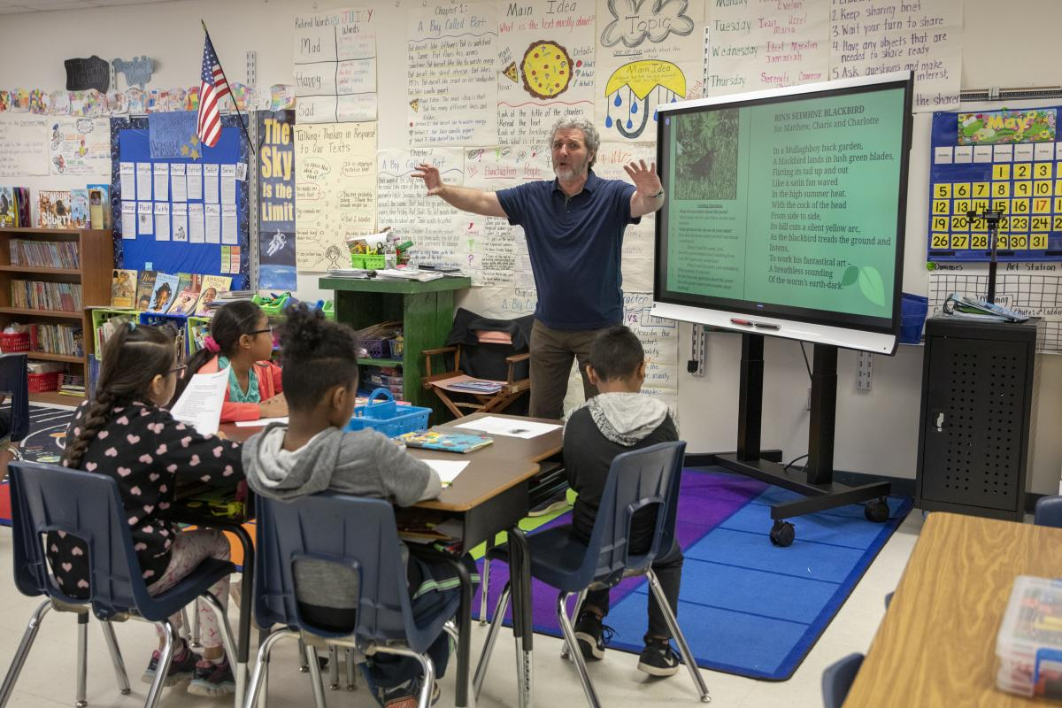 "Rice shares and acts out his poem, ""Rinn Seimhne Blackbird."" Academy third-grade students eagerly watch. Photo by Troy Tuttle"