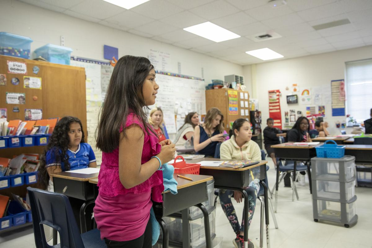 Academy third grader, Itzel Escobar-Torres, shares the first line of her poem. Photo by Troy Tuttle