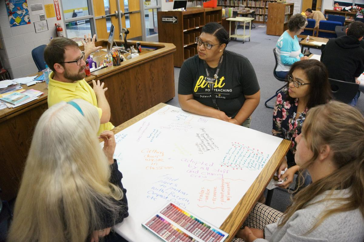 From left to right: 5th grade teacher Cathy Ryan, Kindergarten teacher Matt Hamm, Johnson, Hall-Powell, and Conway consider how the employment of the JustPax mini-grants could help the Academy move forward on action-based learning and classroom projects. Photo by Vachel Miller