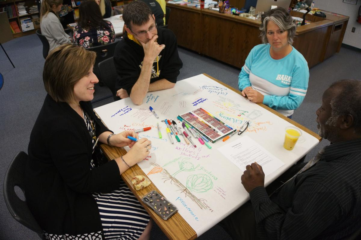 From left to right: Snow '06 '14, 2nd grade teacher Brent Macrow, 1st grade teacher Marla Cantrell, and Hunter discuss community resources that would assist in the construction of a school garden at the Academy. Photo by Vachel Miller