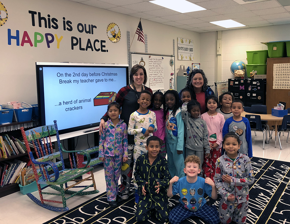 Dr. Amie Snow '01 '09, Director of Curriculum (left), 1st-grade teacher, Melissa Boyd '15 (right), and students get cozy at the Academy's PJ Day.