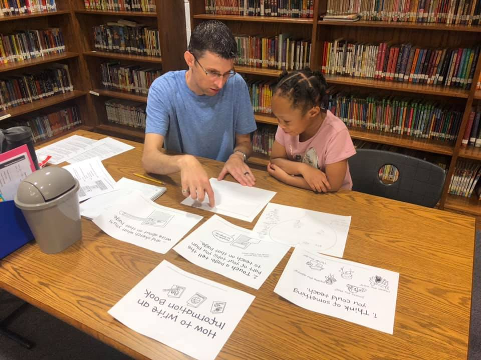 Macrow (left) and rising 1st grader Alicia Spain (right) work on writing nonfiction at the Academy's summer reading clinic. Photo by Amie Snow