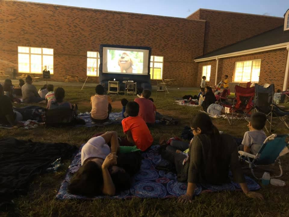 Academy families gather on the blacktop for a movie night under the stars coordinated by the PTO. Photo by Amie Snow