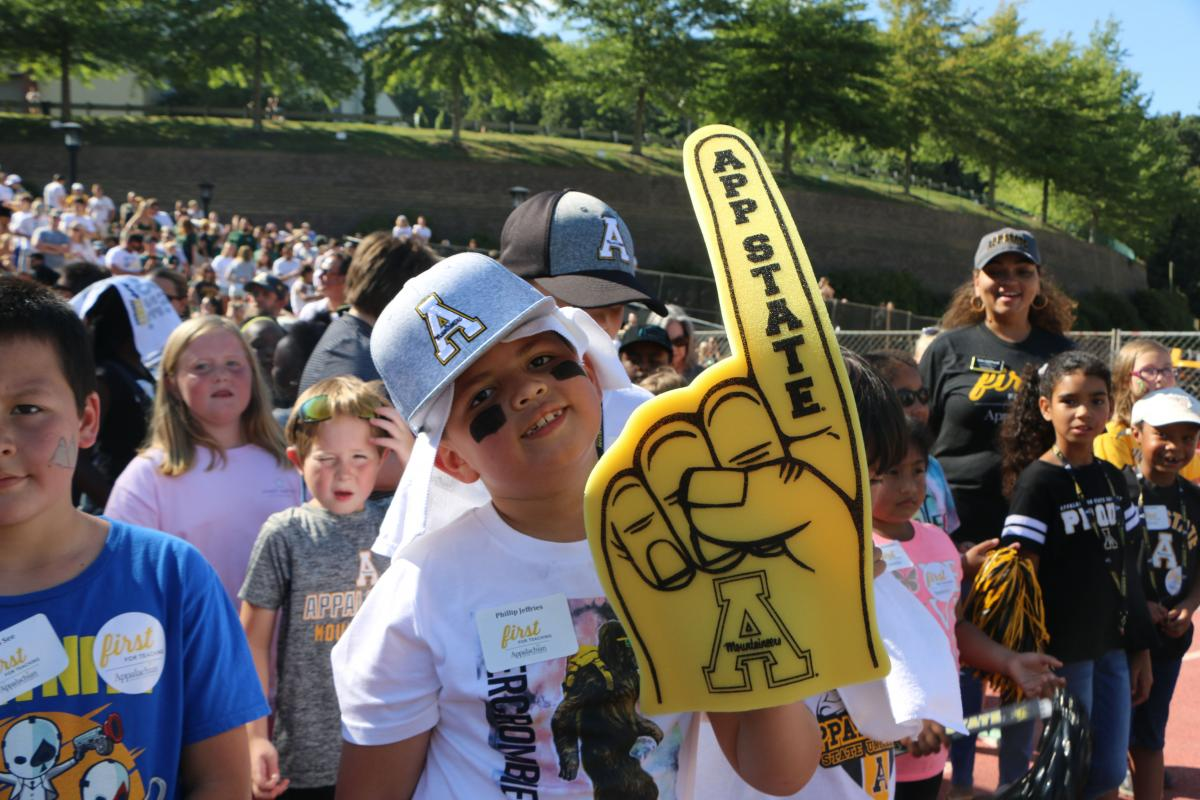 Second grade student and Mountaineer Reader Phillip Jeffries, Jr. shows his Appalachian pride before walking onto the field to be recognized at the Education Day football game. Photo by Rebekah Saylors