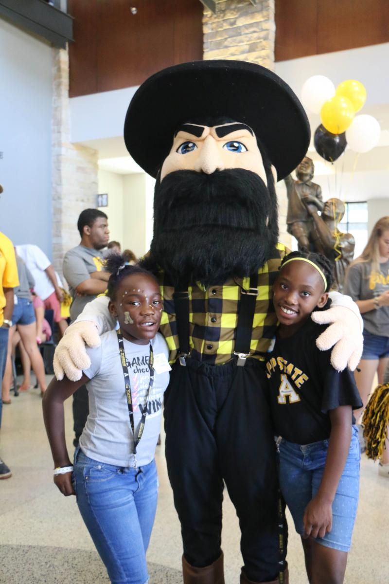 Fifth grade students Myracle Wilson (left) and Tamera Rowland (right) pose with Yosef at the Mountaineer Readers tailgate. Photo by Rebekah Saylors