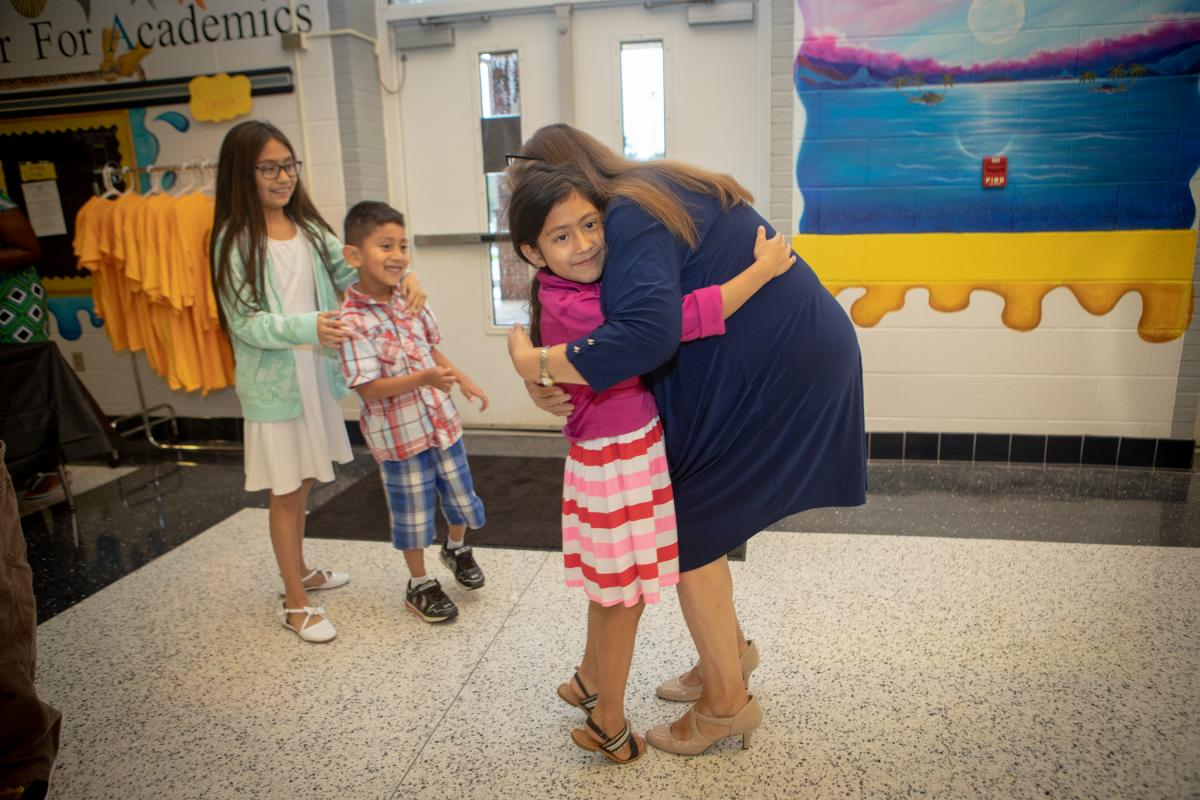 Media Specialist Carla Clayton (right) welcomes back second grade student Arely Espinoza-Caballero (left) with a hug at the Academy's Open House. Photo by Marie Freeman