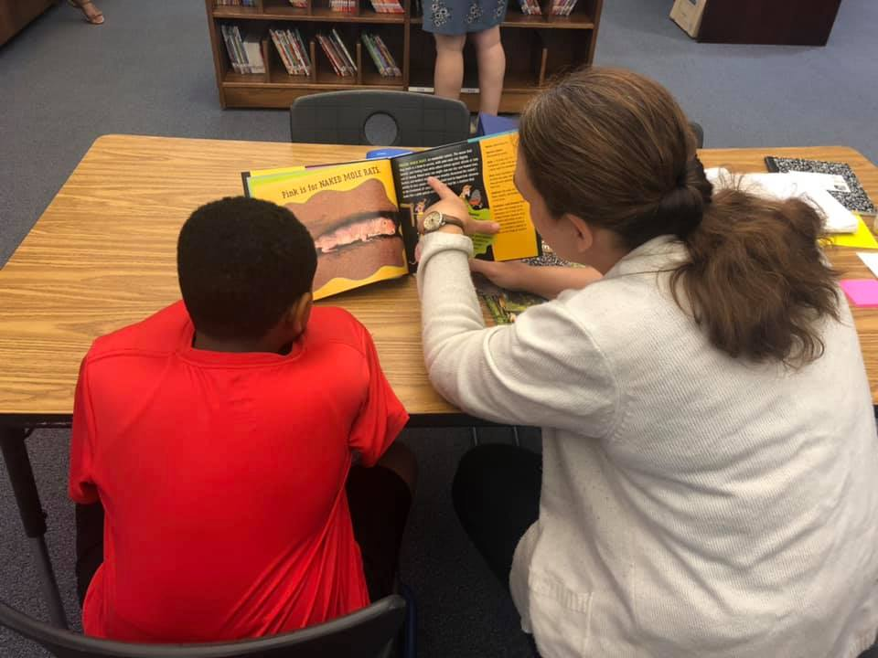 Rising 5th grade Tracen Tyner (left) and reading education graduate student Kim Settlemyre (right) read together at the Academy's summer reading clinic. Photo by Amie Snow