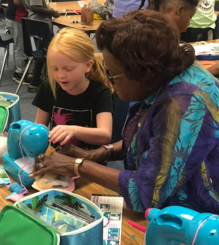 4th grade teacher Wanda McLemore (right) teaches rising 3rd grader Quinlan Hushbeck (left) how to use a sewing machine as part of the Academy's summer enrichment program. Photo by Amie Snow